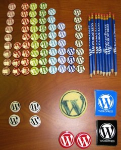 WordCamp swag - buttons, stickers, pencils, and cookie - photo by Lorelle VanFossen.